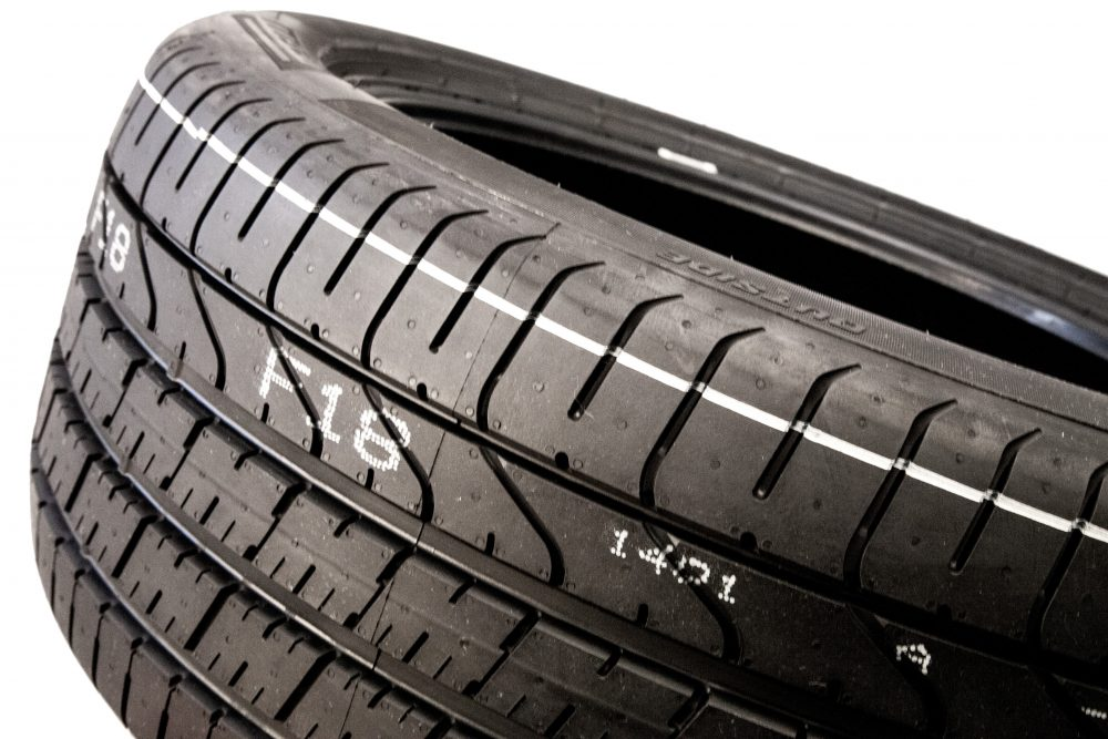 Rubber tire with striping and human readable text mark made by valve jet